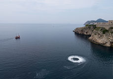 Adriatic sea with tourist cruise boat and seado. Adriatic sea near Dubrovnik, tourist boat and a seado creating a circle of white foam Stock Image