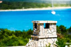 Adriatic sea view of fireplace grill chimney and beach background. Typical view of Croatian coast with fireplace and sailboat on a sunny day stock photos