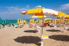 Adriatische Seeküstenansicht Küste von Italien, Sommerregenschirme auf sandigem Strand mit Wolken auf Horizont Lizenzfreie Stockfotos