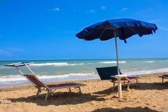 Adriatische Seeküstenansicht Küste von Italien, Sommerregenschirme auf sandigem Strand mit Wolken auf Horizont Stockbilder