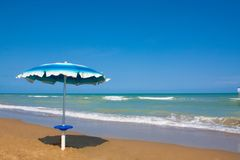 Adriatische Seeküstenansicht Küste von Italien, Sommerregenschirme auf sandigem Strand mit Wolken auf Horizont Stockbild