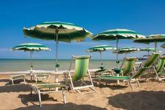Adriatische Seeküstenansicht Küste von Italien, Sommerregenschirme auf sandigem Strand mit Wolken auf Horizont Stockfotos