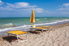 Adriatische Seeküstenansicht Küste von Italien, Sommerregenschirme auf sandigem Strand mit Wolken auf Horizont Lizenzfreies Stockbild