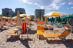 Adriatische Seeküstenansicht Küste von Italien, Sommerregenschirme auf sandigem Strand mit Wolken auf Horizont Lizenzfreies Stockfoto