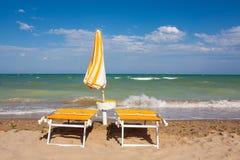 Adriatische Seeküstenansicht Küste von Italien, Sommerregenschirme auf sandigem Strand mit Wolken auf Horizont Lizenzfreie Stockfotografie