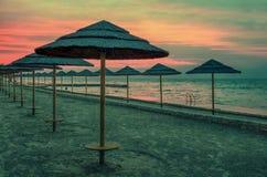 Adriatischer Küstensonnenuntergang mit Strandschirmen Stockfoto