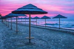 Adriatischer Küstensonnenuntergang mit Strandschirmen Lizenzfreies Stockbild