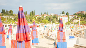Adriatischer Strand mit roten Regenschirmen Stockfoto