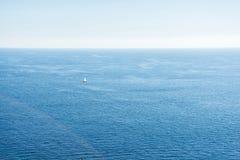 Adriatisches Seeansicht mit einem kleinen Boot mit weißem Segel Ruhiger blauer Himmel des Meerblicks und des freien Raumes Lizenzfreie Stockfotografie