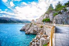 Adriatisches Seeküstenlinie mit drastischem Himmel und Sonnenlicht Felsige Küstenlinie mit den Meereswogen Felsen schlagend klein Lizenzfreies Stockfoto