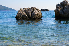 Adriatisches Seeküstenlinie mit roten Felsen und unscharfem Meerwasser Stockfotografie