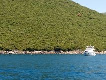 Adriatiskt hav i fjärden av Kotor Montenegro Ett litet fartyg seglar från den branta kusten royaltyfri foto