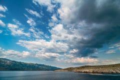 Adriatiskt havfjärd med dramatisk himmel som förbiser Paklenica nationalparkberg arkivbilder