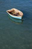 Adrift Rowing Boat. A small rowing boat with no crew adrift on a calm ocean Stock Images