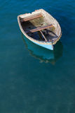 Adrift Rowing Boat. A small rowing boat with no crew adrift on a calm ocean Stock Photography