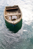 Adrift Rowing Boat. A small rowing boat with no crew adrift on a calm ocean Stock Image