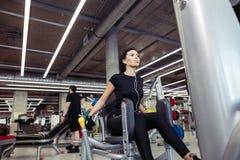 Aducción o máquina del abductor muchacha que ejercita sus piernas en gimnasio Foto de archivo libre de regalías