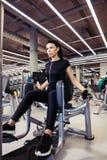 Aducción o máquina del abductor muchacha que ejercita sus piernas en gimnasio Foto de archivo