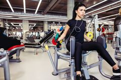 Aducción o máquina del abductor muchacha que ejercita sus piernas en gimnasio Fotos de archivo