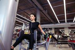Aducción o máquina del abductor muchacha que ejercita sus piernas en gimnasio Fotos de archivo libres de regalías