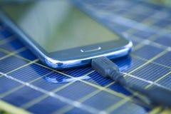 Ładuje telefon komórkowy z słoneczną ładowarką Obrazy Royalty Free
