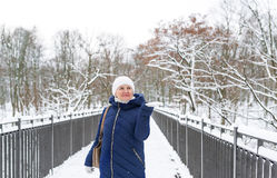 Adult adorable woman wearing blue hooded coat enjoying strolling in winter forest outdoors. Nature cold season freshness concept. Full length portrait Royalty Free Stock Photos