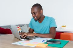 Adult african american man working with computer. At desktop at home office Stock Photography