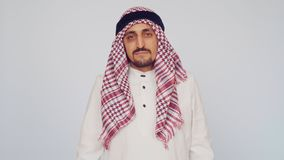 Adult Arab man in national dress on a white background. Saudi Arabian businessman dissatisfied. stock video footage