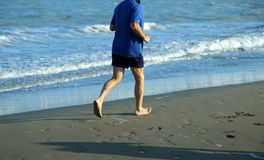 Adult athlete runs on the Sea Beach to keep fit Stock Photography