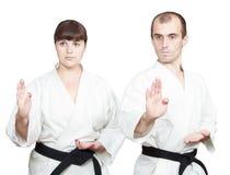 Adult athletes with black belts are doing block Shuto-uke stock images