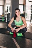 Smiling sportswoman with bottle in gym stock photo