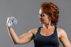 Adult athletic fitness red-haired woman in sports uniform with a bottle of water Stock Photo