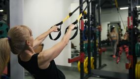 Adult athletic woman doing exercises on the TRX in the sports club 4K Slow Mo. Adult athletic woman doing exercises on the TRX in the sports club stock video footage