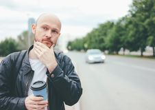 Adult attractive bald bearded man with paper cup of coffee and catching taxi in city street stock image