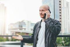 Adult attractive bald bearded man talking by mobile at city street royalty free stock photos