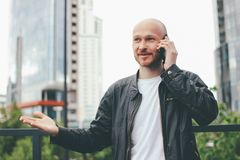 Adult attractive bald bearded man talking by mobile at city street stock image
