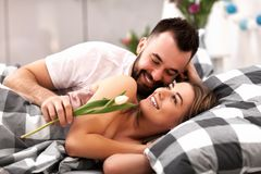 Adult attractive couple in bed with present Royalty Free Stock Photo