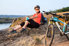 Adult attractive female cyclist is resting. Royalty Free Stock Photography