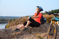 Adult attractive female cyclist is resting. Royalty Free Stock Images