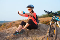 Adult attractive female cyclist sits on the rock and makes the p Royalty Free Stock Images