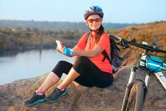 Adult attractive female cyclist smiling. Royalty Free Stock Images