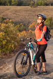 Adult attractive female cyclist standing with closed eyes and en Royalty Free Stock Images