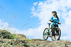 Adult attractive female cyclist  standing on a rock with her mou Royalty Free Stock Photo