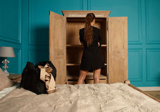 Adult attractive girl in hotel room. Attractive young woman near empty closet in hotel room stock images