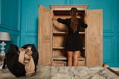 Adult attractive girl in hotel room. Attractive young woman opens door of empty closet in hotel room royalty free stock photography