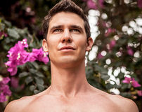 Adult attractive man pose siting in perfect tropical garden. Stock Photos