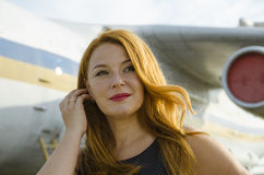 Adult attractive redhead woman about aircraft outside Stock Photos