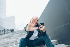 Adult bald bearded serious man with mobile sitting in stair closing camera by hand, no more photo royalty free stock image