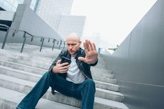 Adult bald bearded serious man with mobile sitting in stair closing camera by hand, no more photo stock photos