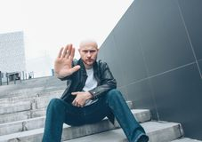 Adult bald bearded serious man with mobile sitting in stair closing camera by hand, no more photo royalty free stock photography